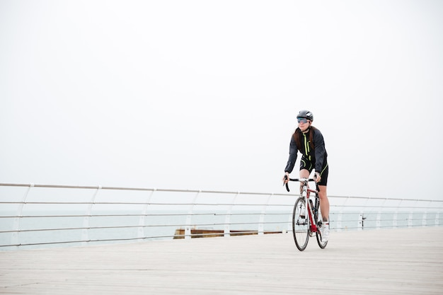 Woman riding on a bicycle outdoors on the beach