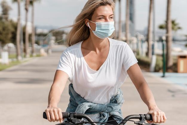 La donna in sella a una bicicletta mentre indossa una maschera medica