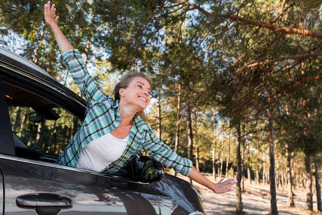 Woman riding the car and holding her hands in the air