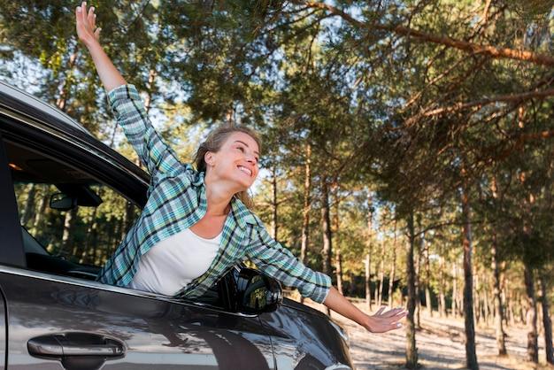Donna in sella alla macchina e tenendo le mani in aria