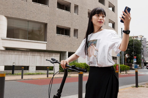 Woman riding electric bicycle in the city and holding smartphone