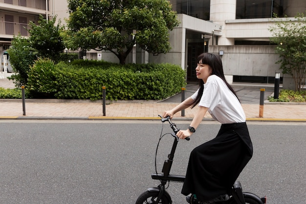 Woman riding electric bicycle in the city