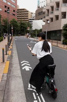 Женщина катается на электрическом велосипеде в городе и держит смартфон