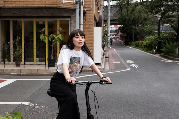 Donna in sella a uno scooter elettrico in città