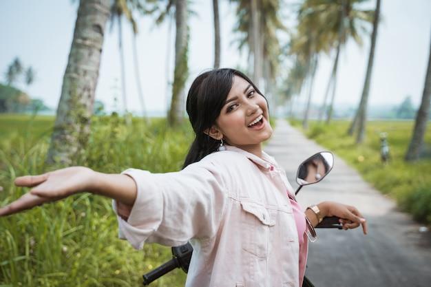 熱帯の田舎道で彼女のスクーターバイクに乗る女性
