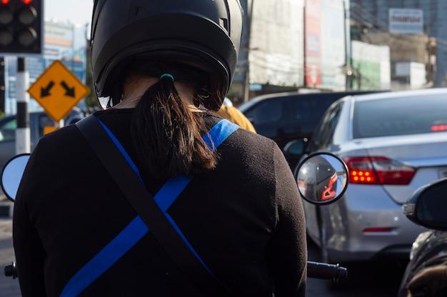 ヘルメットをかぶってバイクに乗る女性が信号を待つ