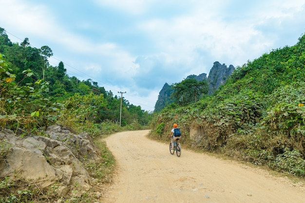 Woman riding mountain bike on dirt road in scenic landscape around vang vieng backpacker travel destination in laos