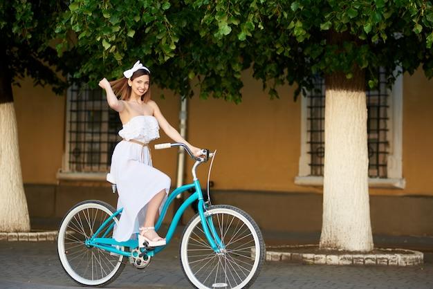 都市の青い自転車夏に乗る女性