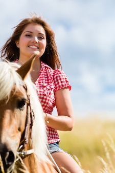 여름 초원에서 말을 타고 여자
