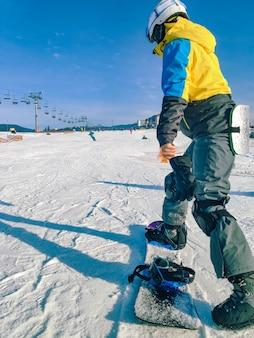 片足でスノーボードに乗っている女性は、ウィンター山のアクティビティに固定されていません。コピースペース
