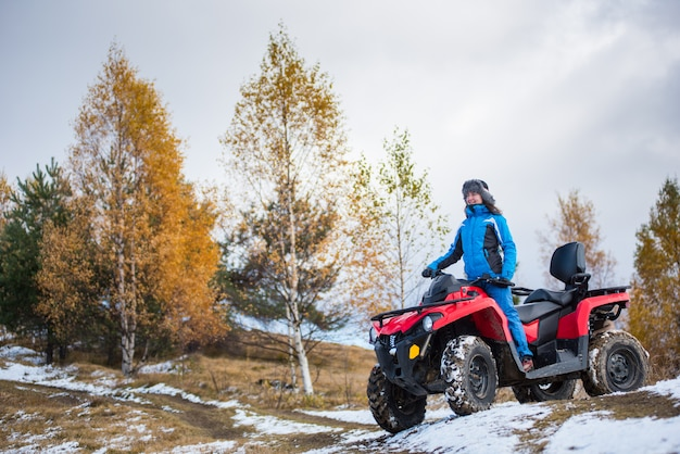 Woman riding on a red quadbike atv on snow-covered hill against autumn nature