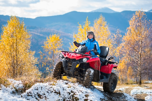 Woman riding a red quadbike on snow-covered hill at sunny day