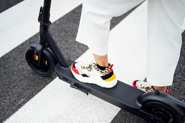 夏に横断歩道でスクーターに乗る女性