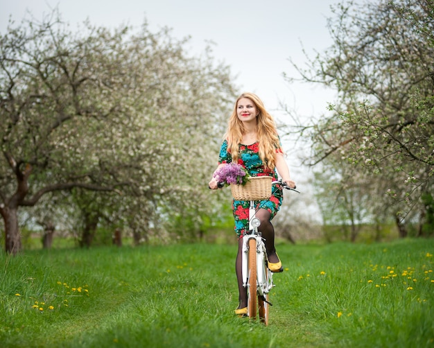 Woman riding a white city bicycle in spring garden