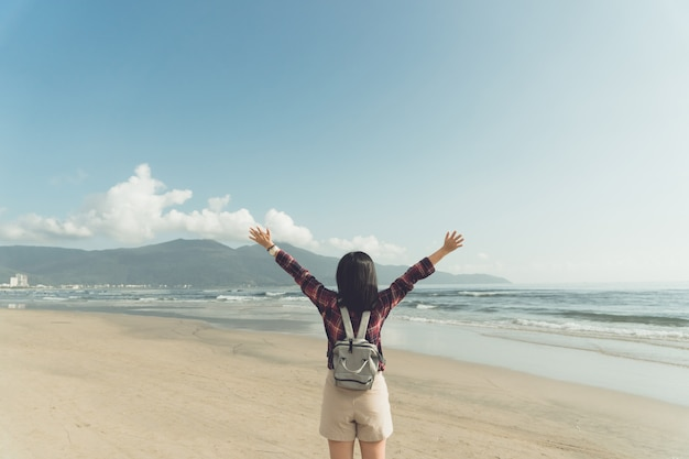 Woman rise hands up to sky freedom concept with blue sky and summer