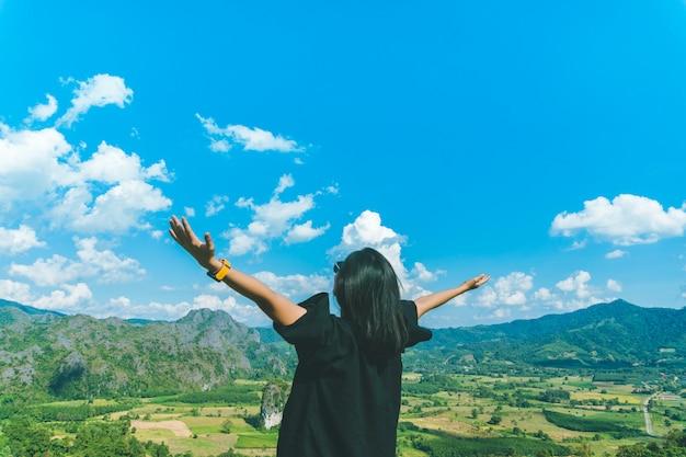 Руки подъема женщины до концепции свободы неба с голубым небом.