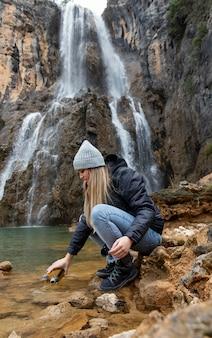 Donna in acqua di raccolta del fiume