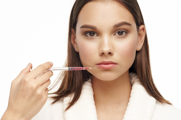 Woman in robe injecting botox in her face skin care