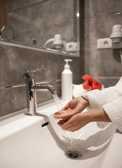 A woman in a robe washes her hands under running water from a tap.