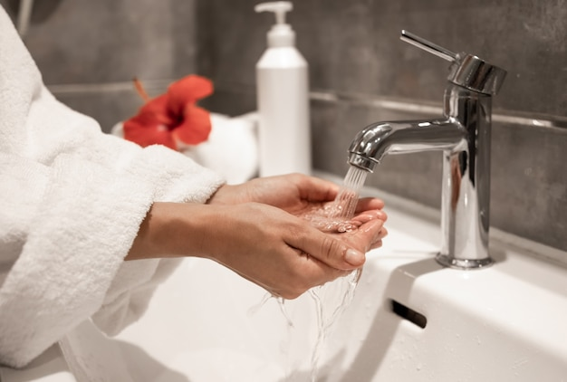 A woman in a robe washes her hands under running water from a tap