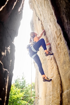Woman rock climbing with rope on a steep rock wall