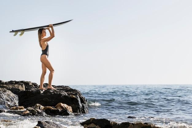 Woman on rocky sea shore holding surfboard on head