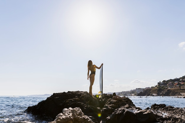 Woman on rocky sea shore with surfboard looking at sea