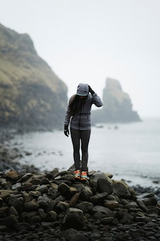 Woman at a rocky shore at spar cave, isle of skye