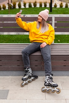 Woman in roller blades taking a selfie on bench