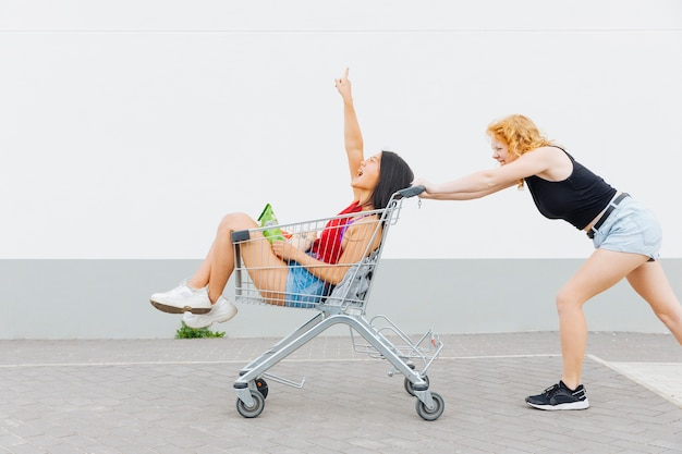 Woman rolling girlfriend in shopping trolley