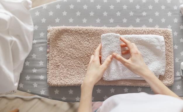 Женщина прокатывает гладильные чистые полотенца, стоя у гладильной доски