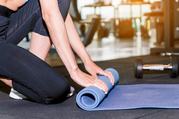 Woman rolling mat in gym