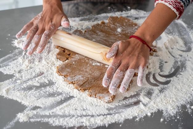 麺棒でジンジャーブレッド生地を伸ばす女性