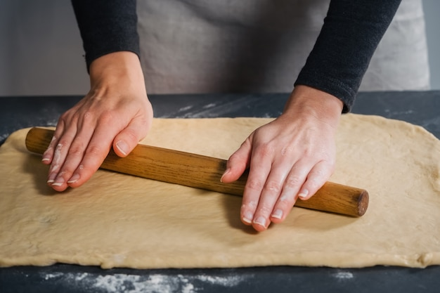 石のテーブルの上でおいしいパンのために生地を広げている女性
