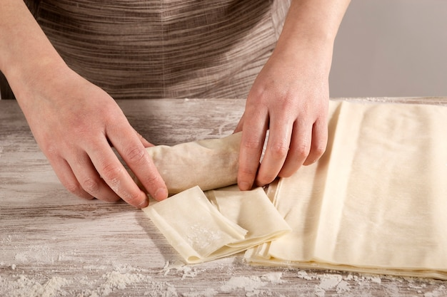 Woman rolling up phyllo pasta filled with tuna to cook a recipe