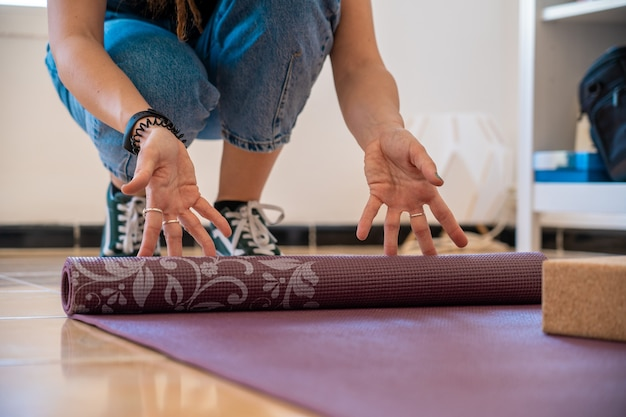 Woman rolling yoga mat at home