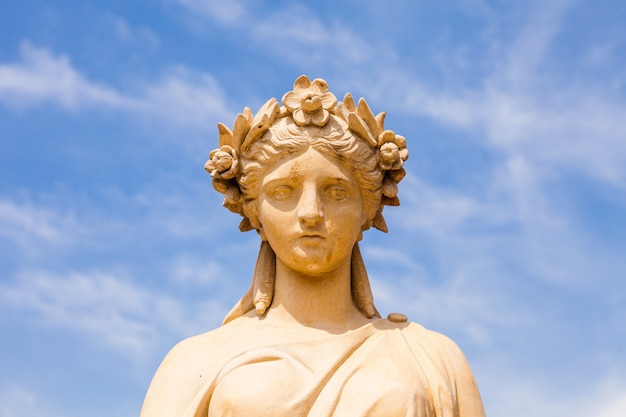 Woman roman statue on blue sky close up