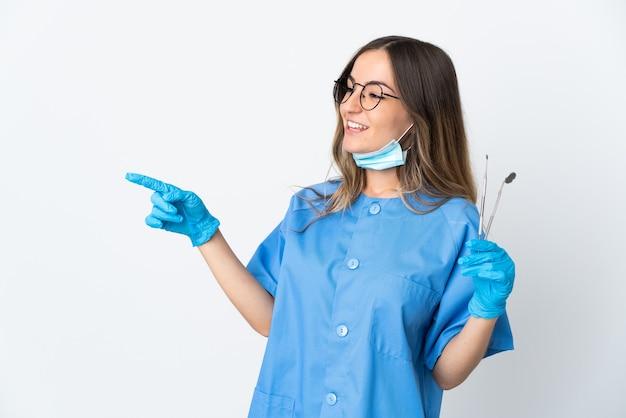 Женщина-стоматолог из румынии держит инструменты над изолированной на розовой стене, указывая пальцем в сторону и представляет продукт