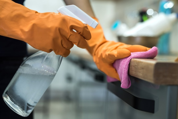 Woman in rubber gloves cleaning the kitchen counter