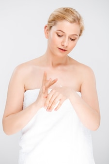 Woman rubbing cream on hands, wear towel