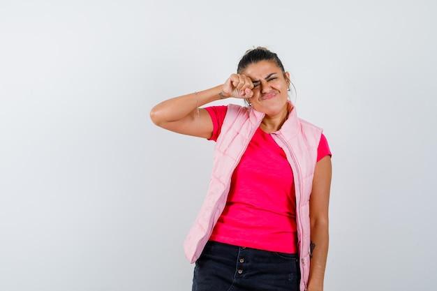 Donna che si sfrega gli occhi mentre piange in maglietta, gilet e sembra offesa