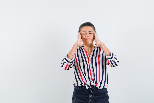 Женщина потирает виски в рубашке, юбке и выглядит уставшей
