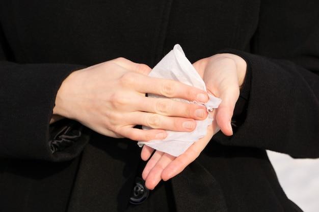 여자는 젖은 닦음으로 그녀의 손을 티 나지