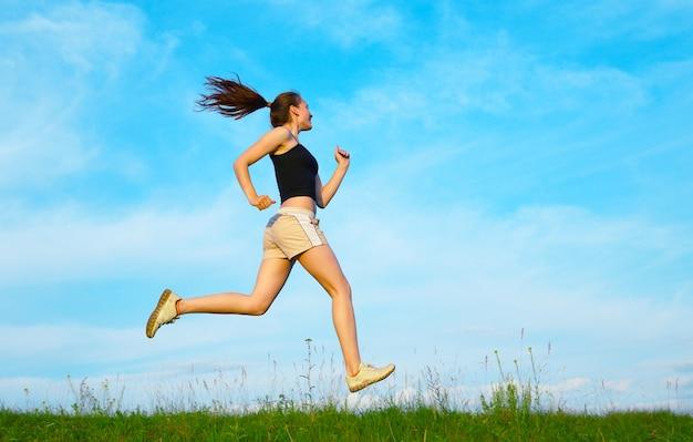 空の下の緑の芝生の上を走る女性