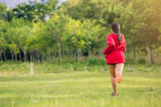 석양에 푸른 잔디 필드에서 운동을 실행하는 빨간 후드에 여자 주자 운동 선수