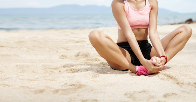 Женщина-бегун делает растяжку бабочки, кладет руки на стопы во время разминки на пляже перед бегом, готовит ноги к кардиотренировке, сидит на пляже на фоне размытого моря