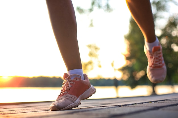Woman runner legs and shoes in action on road outdoors at sunset.