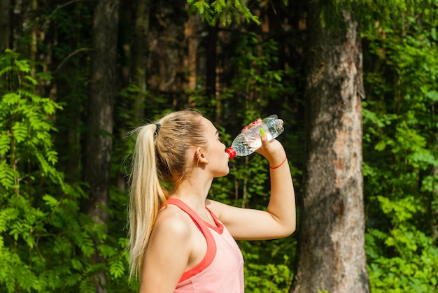Woman runner quenches thirst from a plastic bottle while jogging through the forest