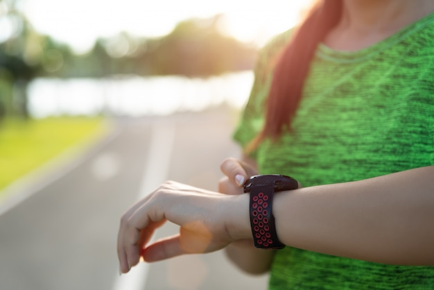 Бегун женщины настраивая умные часы перед бежать во время захода солнца.