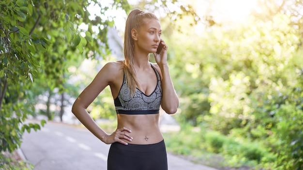 Женщина-бегун, стоя перед тренировкой в парке летом говорить по телефону.